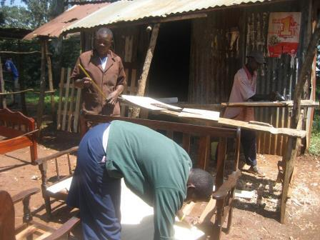 Victor Otieno (links) und zwei Handwerker vor der Werkstatt